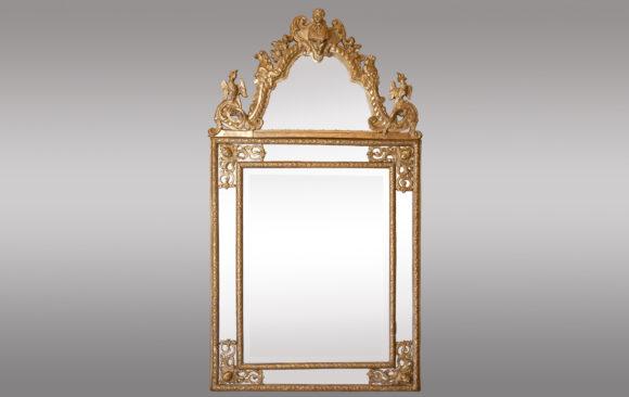 Espejo Regencia <br/> en madera tallada a la berain y dorada<br/> Siglo XVIII